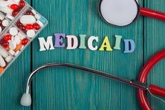 Text & x22; Medicaid& x22; av kulöra träbokstäver, stetoskopet och preventivpillerar royaltyfri foto