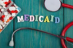 Text & x22;Medicaid& x22; of colored wooden letters, stethoscope and pills. On a blue wooden background Royalty Free Stock Photo