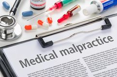 Medical malpractice written on a clipboard. The text Medical malpractice written on a clipboard royalty free stock image