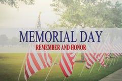 Text Memorial Day e a honra na fileira de bandeiras americanas do gramado imagens de stock