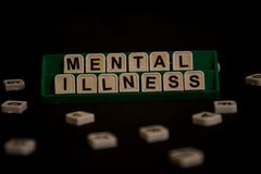 Text `mental illness` on uppercase letters. On black background stock photography