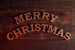 Text merry christmas. gold letters on a brown wooden background. Top view of the new year. Christmas. holidays royalty free stock photography