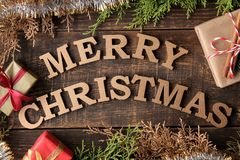 Text merry christmas. gold letters and gift and christmas tree branches on brown wooden background. Top view of the new year. Chri. Text merry christmas. gold royalty free stock photos