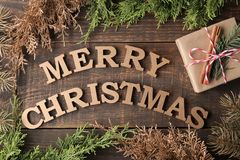 Text merry christmas. gold letters and gift and christmas tree branches on brown wooden background. Top view of the new year. Chri. Stmas. holidays royalty free stock photos