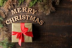 Text merry christmas. gold letters and gift and christmas tree branches on brown wooden background. Top view with space for inscri. Ption. new Year. Christmas stock images