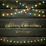 Colorful Christmas lights on black wooden background. Text Merry Christmas and Happy New Year with colorful Christmas lights. Holiday decorations on black Stock Photography