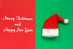 Text Merry Christmas and Happy New Year, Red Claus hat o. Text Merry Christmas and Happy New Year. Red Claus hat on two-tone red and green background. Top view royalty free stock images