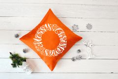 Text Merry Christmas on orange pillow a white wooden christmas background. Flat lay, top view photo mockup.  royalty free stock images