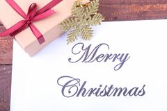 Text merry christmas on paper with many balls and gift boxes Stock Photos