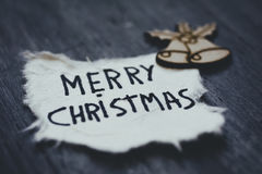 Text merry Christmas in a piece of paper Stock Photography