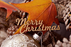 Text merry christmas, pine cones and bauble Stock Images