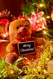 Text merry christmas, teddy bear and gifts under a christmas tre Stock Photos
