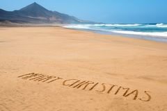 Text merry christmas in the sand of a beach royalty free stock photography