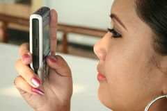 Text message. A filipina sending a text message Stock Image