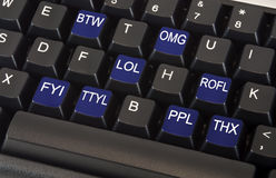 Text message keyboard. Black keyboard with text message slang words on keys including LOL, OMG, BTW, ROFL, FYI, TTYL, PPL and THX to illustrate fast paced social Stock Photos