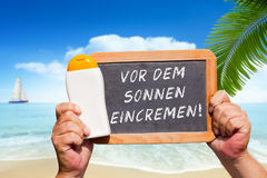 Text message - Vor dem Sonnen eincremen on a slate Stock Images