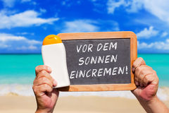 Text message - Vor dem Sonnen eincremen on a slate Royalty Free Stock Photos