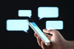Text messages in cellphone screen with abstract hologram speech bubbles. Instant messaging app. Texting, group chat, sexting.