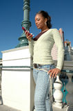 Text Messaging. Beautiful Black woman standing outside in a city scene using her cell phone. Woman with expressions on her face as she uses her cell phone. Text Royalty Free Stock Photography