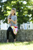 Text messaging. Little girl sending text messaging with mobile phone while sitting outdoors Stock Photos