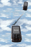 Text messaging. Two cellphones against a coudy sky symbolizing the sending of messages to each other with a clipping path Stock Photography