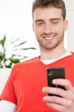 Text messaging with mobile phone. Smiling young man browsing and text messaging on his smart phone at home Royalty Free Stock Photo