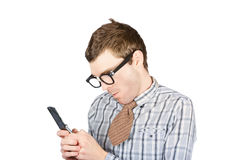 Text messaging nerd. Isolated photograph of a dorky man concentrating while text messaging on smart mobile phone, over white background Royalty Free Stock Image