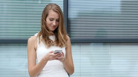 Text Messaging on Smartphone by Beautiful Girl, Outside Office stock footage