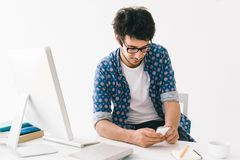 Text messaging. Young man text messaging while sitting at the desk Stock Photo