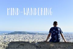 Text mind-wandering and man observing the city. The text mind-wandering and a young caucasian man, seen from behind, at the top of a hill observing the city and Royalty Free Stock Photography