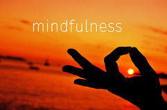 Text mindfulness and hand in gyan mudra at sunset Stock Photo
