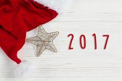 Text mit 2017 Zeichen auf Weihnachtsgoldenem Stern und Sankt-Hut auf weißem r Stockfotografie