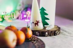 Text mit 2017 Zeichen auf Weihnachtsrustikaler Tabelle mit Kerze mit reinde Lizenzfreies Stockbild
