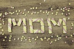 Text MOM written with marshmallows. Mother`s day concept. Spring holidays. On wooden background. Text MOM written with marshmallows. Mother`s day concept Stock Photo