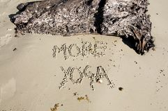 Text `More Yoga` written in the sand on a sunny day royalty free stock photos