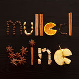 Text mulled wine made from slice of orange, spices on the black Stock Photos