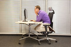 Text neck - man in slouching position working with computer Royalty Free Stock Image
