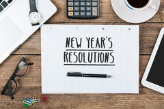 Text new years`s resolutions on note, Office desk with computer Stock Image