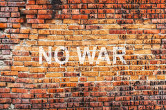 Text NO WAR on stained old orange brick wall texture background Royalty Free Stock Photos