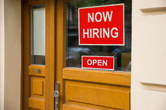 The Text Now Hiring Sticker Attached On Door. The Text Now Hiring Sticker Attached On Glass Door Of The Office Royalty Free Stock Photos