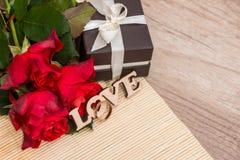 Text o amor com alianças de casamento, caixa de presente e as rosas vermelhas Imagem de Stock