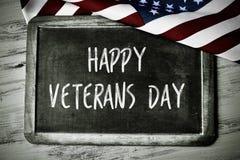 Text o dia de veteranos feliz e a bandeira dos E.U. fotos de stock