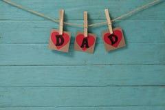 Text o paizinho nas formas do coração que penduram na parede verde Imagem de Stock