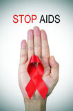 Text o SIDA da parada e uma fita vermelha em uma mão do homem Fotos de Stock Royalty Free