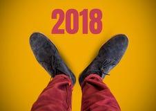 2018 text och grå färgskor på fot med gul bakgrund Royaltyfria Foton