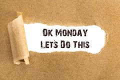 The text Ok Monday Lets Do This appearing behind torn brown paper.  stock image