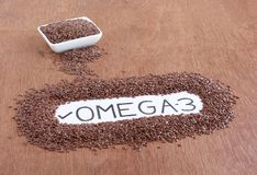 Text `Omega-3` Handwritten on a Paper Surrounded by Flax Seed. Text `Omega-3` handwritten on a paper, using pencil, to highlight a trait of flax seeds that they stock image