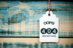 Page not found, 404 Error. Text 'OOPS ! 404 PAGE NOT FOUND' inscribed on a price / sales label hanging by a thread in front of boards of distressed wood royalty free stock images