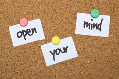 Text Open Your Mind. Written on pinned white stickers royalty free stock photo