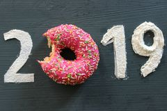 Text 2019, pink donut in glaze. Text 2019 on black textured, pink donut in glaze instead of the number 0, new year`s concept royalty free stock photo